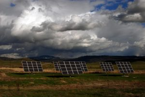 Solar panels tolerate wind speeds in open country with clouds and cows